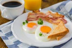 与晴朗的边的美国早餐鸡蛋、烟肉、多士、薄煎饼、咖啡和汁液 免版税库存图片