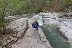 与绿松石池塘的美丽的在山的峡谷和瀑布,游人沿足迹走了 旅客女孩 库存照片