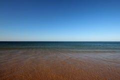 与绿松石海的红色海滩 免版税库存图片
