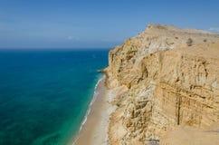 与绿松石海洋的印象深刻的峭壁在Caotinha,安哥拉的海岸的 库存图片