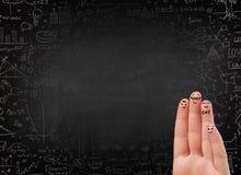 与黑黑板的愉快的手指面带笑容在背景中 库存照片