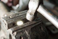 与1枚欧洲硬币和锤子的台式虎钳 库存图片