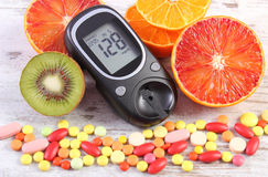 与结果的Glucometer、果子和五颜六色的医疗药片、糖尿病、健康生活方式和营养 免版税库存图片