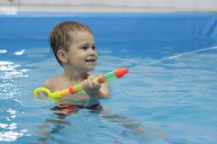 与水枪的小男孩射击在游泳池 图库摄影