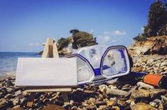 与画架的减速火箭和葡萄酒神色图象概念空白白色帆布框架在海滩 潜水风镜和废气管在ston适应 免版税库存照片