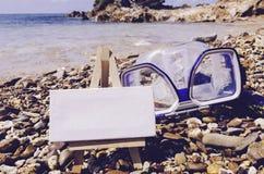 与画架的空白的白色帆布框架在海滩 潜水风镜和废气管在石头适应 免版税库存照片