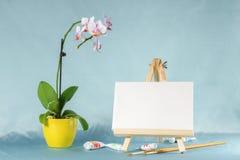 与画架的静物画有一空白的帆布、水彩和orchi的 图库摄影