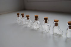 与黄柏停止者的微型玻璃瓶不同的形式在白色背景 免版税库存图片
