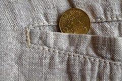与10欧分的衡量单位的欧洲硬币在破旧的亚麻布裤子的口袋的 库存图片