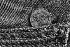 与10欧分的衡量单位的欧洲硬币在破旧的牛仔布牛仔裤的口袋,单色射击的 库存图片