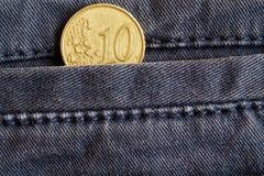 与10欧分的衡量单位的欧洲硬币在老蓝色牛仔布牛仔裤的口袋的 免版税图库摄影