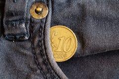与10欧分的衡量单位的欧洲硬币在老被穿的蓝色牛仔布牛仔裤的口袋的 免版税库存图片