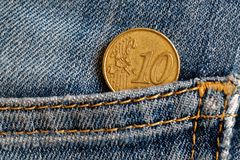 与10欧分的衡量单位的欧洲硬币在蓝色被穿的牛仔布牛仔裤的口袋的 免版税库存图片