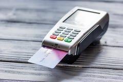 与付款终端的购买由在木背景的卡片 库存图片