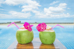与水池的热带新鲜的椰子鸡尾酒和海滩在海洋,普吉岛,泰国 免版税图库摄影