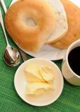 与黄油奶油和咖啡的百吉卷 免版税库存照片