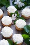 与黄油奶油和春天白花的杯形蛋糕 免版税库存照片