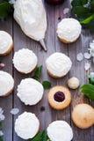 与黄油奶油和春天白花的杯形蛋糕 库存照片