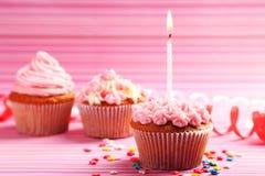 与黄油奶油和蜡烛的生日杯形蛋糕在五颜六色的背景 免版税库存照片