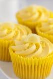 与黄油奶油漩涡和坦率的果子装饰的柠檬杯形蛋糕 免版税图库摄影