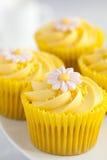 与黄油奶油漩涡和方旦糖的柠檬杯形蛋糕开花装饰 免版税库存图片