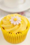 与黄油奶油漩涡的柠檬杯形蛋糕和方旦糖开花装饰 免版税库存照片