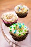 与黄油奶油的鲜美五颜六色的杯形蛋糕 库存图片
