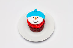与黄油奶油结冰的圣诞节杯形蛋糕在茶碟 雪人 免版税库存图片