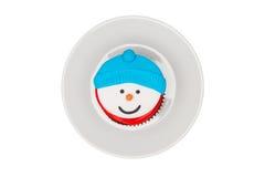 与黄油奶油结冰的圣诞节杯形蛋糕在茶碟 雪人 免版税图库摄影