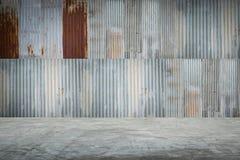 与水泥地板的老金属板屋顶纹理 免版税库存照片