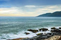 与水海的太阳上升挥动飞溅在海岩石 库存照片
