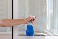 与洗涤剂的Houseworker干净的塑料pvc窗口 免版税库存图片