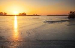 与冻湖和日落火热的天空的冬天风景 免版税库存照片