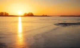 与冻湖和日落火热的天空的冬天风景 库存照片