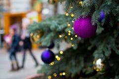 与购物在背景中的被弄脏的人民的圣诞树细节 免版税图库摄影
