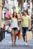 与购物袋的微笑的年轻对在城市 库存图片