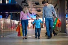 与购物袋的年轻家庭 库存照片