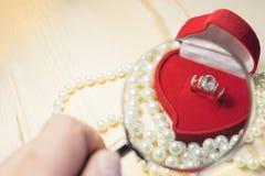 与黄玉的金黄圆环在一个红色礼物盒 免版税库存照片