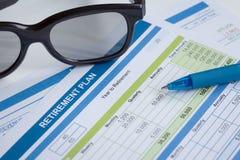 与玻璃和笔,企业概念的退休计划 免版税库存照片