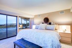 与玻璃墙和出口的可爱的卧室设计对露台 图库摄影