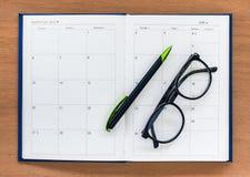 与玻璃的日志计划者书开放日历在Th的页和笔 免版税图库摄影