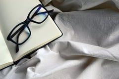 与玻璃的笔记薄在床上 免版税图库摄影