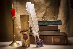 与玻璃的葡萄酒静物画在旧书临近墨水瓶架、羽毛、老纸和灼烧的蜡烛在帆布背景 免版税库存照片