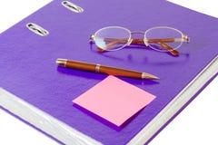 与玻璃的紫罗兰色在白色背景的文件夹和笔 免版税图库摄影