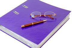 与玻璃的紫罗兰色在白色背景的文件夹和笔 免版税库存图片