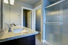 与玻璃阵雨和砖地的明亮的卫生间内部 库存照片