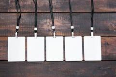与绳索的五枚卡片徽章在木桌上 库存照片