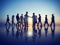 与他们的同事一起的两个商人握手 库存图片