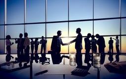 与他们的同事的商人握手 免版税库存照片
