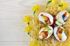 与水仙的复活节彩蛋在木背景 免版税库存图片